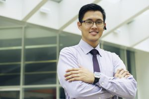 Portrait of confident asian businessman. The man stands in a street against office buildings and crosses arms looking at camera with bluetooth headset and smartwatch